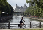 A cyclist pedals along side the Rideau Canal in Ottawa, Monday June 19, 2006, with the historic Chateau Laurier in the background, where the Rideau Canal flows into the Ottawa River. Ontario's Rideau Canal system, a 202-kilometre long historic waterway that is vying for recognition as a UNESCO World Heritage Site. (CP/ Fred Chartrand)