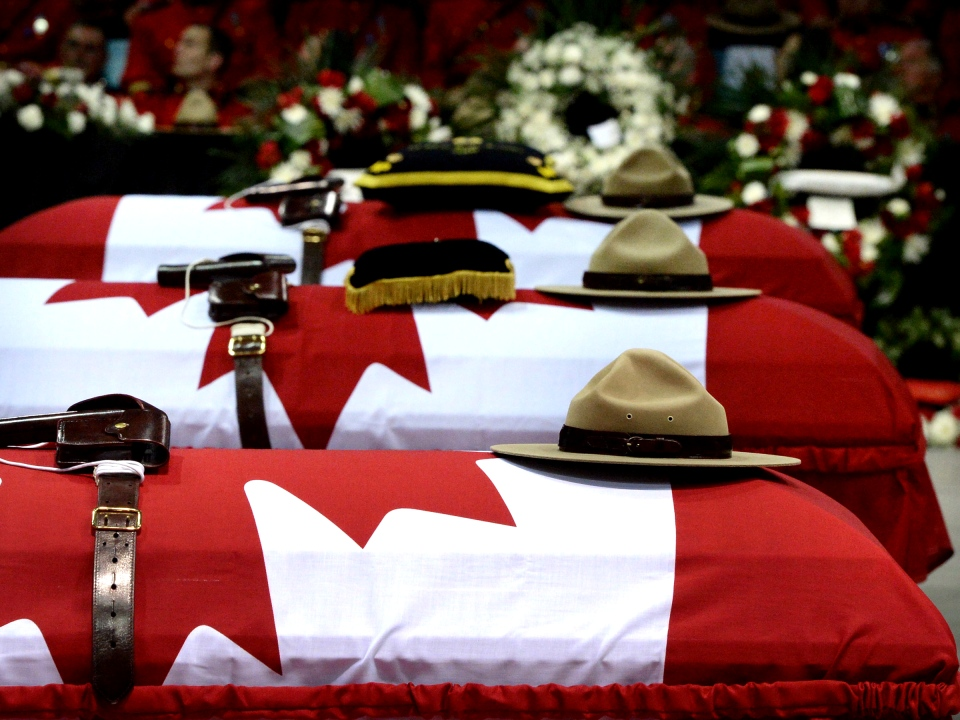 Stetsons rest on the caskets of the three slain RCMP officers, Const. Dave Ross, Const. Douglas Larche and Const. Fabrice Gevaudan at a regimental funeral in Moncton, N.B., Tuesday, June 10, 2014. (Sean Kilpatrick / THE CANADIAN PRESS)
