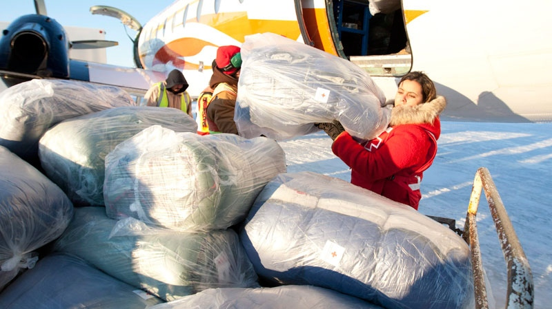 A Red Cross worker loads sleeping bags onto a trailer at the airport in Attawapiskat, Ont., Tuesday November 29, 2011. (Adrian Wyld / THE CANADIAN PRESS)