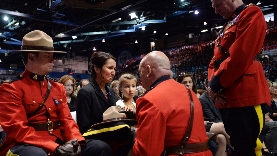 RCMP Commissioner Bob Paulson presents Const. Fabrice Georges Gevaudan's widow Angela with her husband's Stetson at a regimental funeral for three slain RCMP officers in Moncton, N.B., Tuesday, June 10, 2014. (Sean Kilpatrick / THE CANADIAN PRESS)