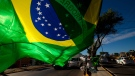 FILE - A street vendor sells representations of Brazil's national flags near the Arena Castelao in Fortaleza, Brazil, Wednesday, June 11, 2014. (AP / Fernando Llano)