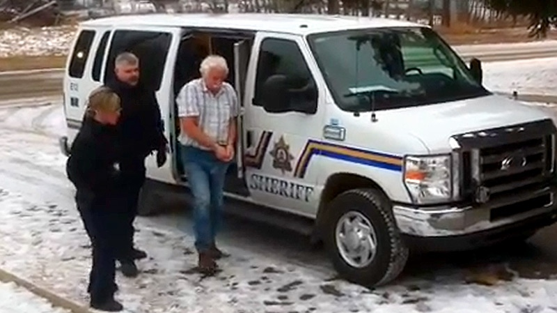 RCMP officers lead Daniel Stoesz into the Lac La Biche courthouse on Monday, December 5.