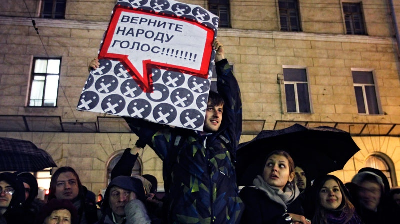 A man holding a banner which reads 'Return the vote ability to people!' attends a rally in Moscow, Monday, Dec. 5, 2011. (AP / Sergey Ponomarev)