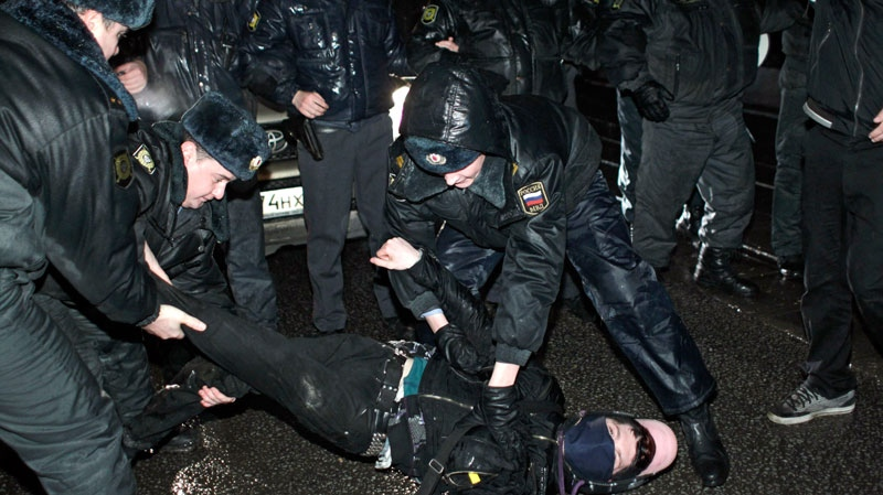 Police officers detain a protester after a rally in downtown Moscow, Monday, Dec. 5, 2011. (AP Photo/Sergey Ponomarev)
