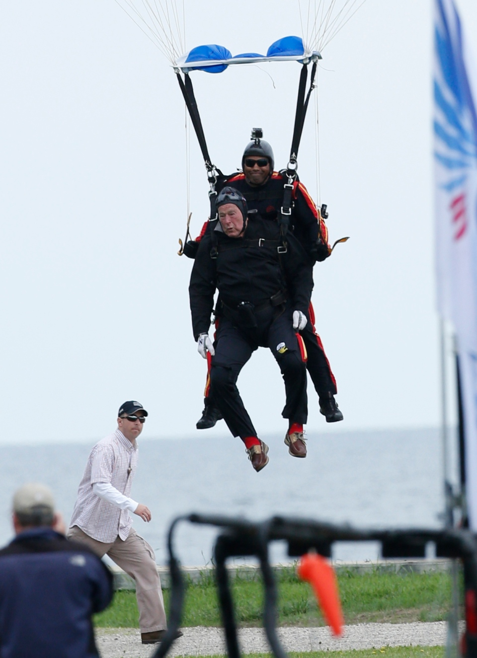 Former President George H.W. Bush, strapped to Sgt. 1st Class Mike Elliott, prepares to land while celebrating Bush's 90th birthday in Kennebunkport, Maine, Thursday, June 12, 2014. (AP Photo/Robert F. Bukaty)