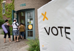Voters arrive at a polling station in Toronto to cast their vote for the Ontario provincial election on Thursday, June 12, 2014. (Darren Calabrese / THE CANADIAN PRESS)