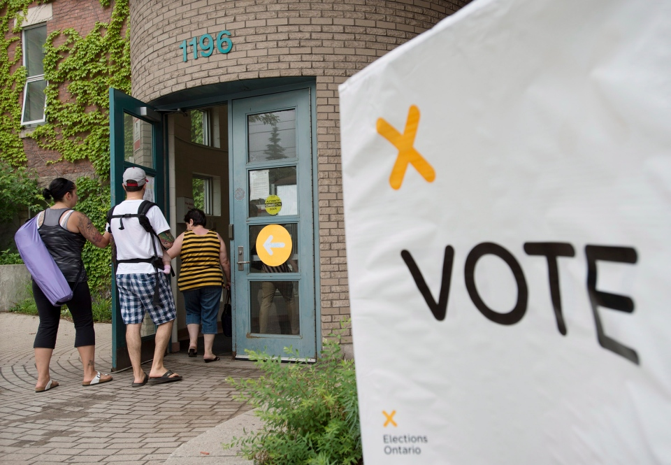 Voters arrive at a polling station in Toronto to cast their vote for the Ontario provincial election on Thursday, June 12, 2014. (The Canadian Press/Darren Calabrese)