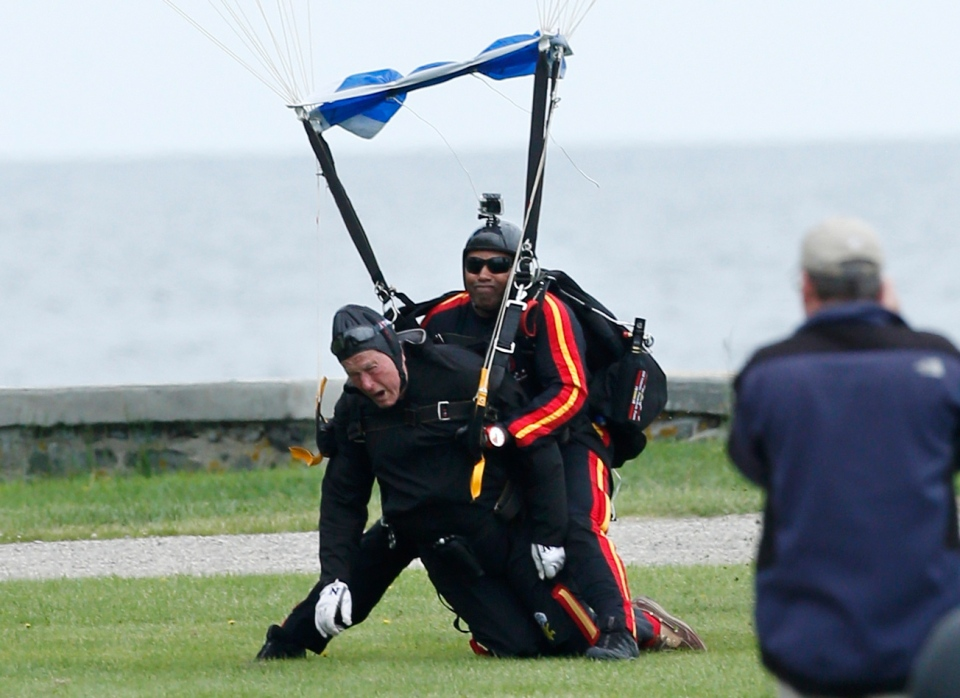 Former U.S. President George H.W. Bush, left, strapped to Sgt. 1st Class Mike Elliott, land on the lawn at St. Anne's Episcopal Church after making a tandem parachute jump near Bush's summer home in Kennebunkport, Maine, Thursday, June 12, 2014. (AP Photo/Robert F. Bukaty)