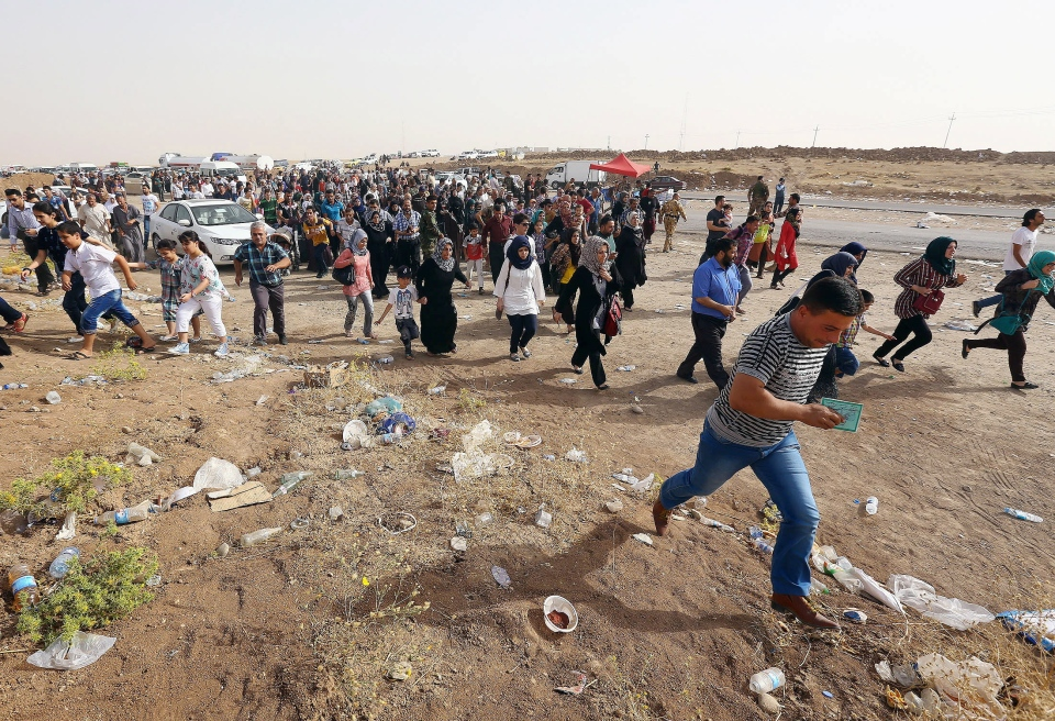Refugees fleeing from Mosul head to the self-ruled northern Kurdish region in Irbil, Iraq, 350 kilometres north of Baghdad, Thursday, June 12, 2014. (AP Photo)