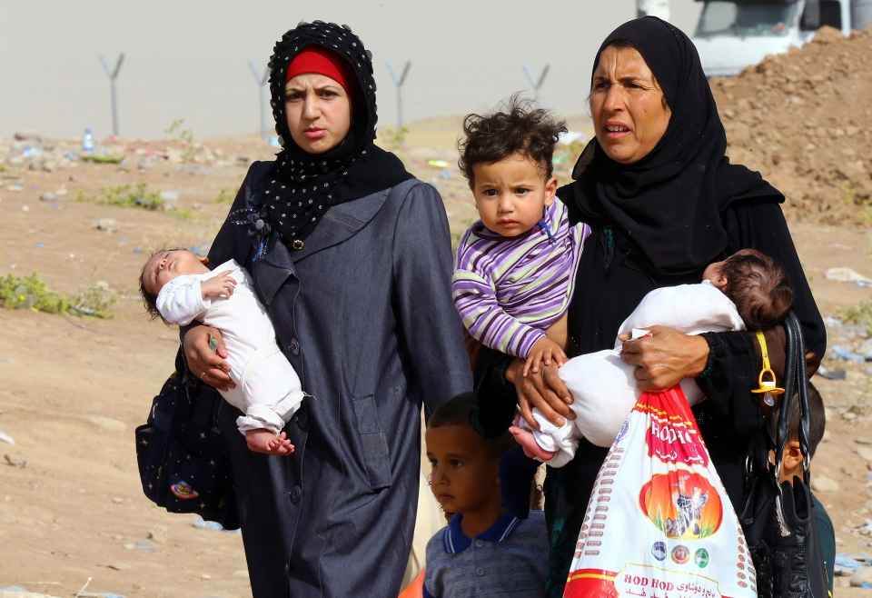 Iraq refugees fleeing from Mosul head to the self-ruled northern Kurdish region, as they walk past an area in Irbil, Iraq, 350 kilometres north of Baghdad, Thursday, June 12, 2014. (AP Photo)