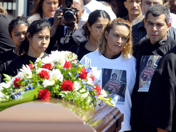 Gilberto and Lilian Villanueva (right) the parents of Fredy Villanueva, and other family members pass by the coffin at his funeral in Montreal, Thursday August 14, 2008. (Graham Hughes / THE CANADIAN PRESS)