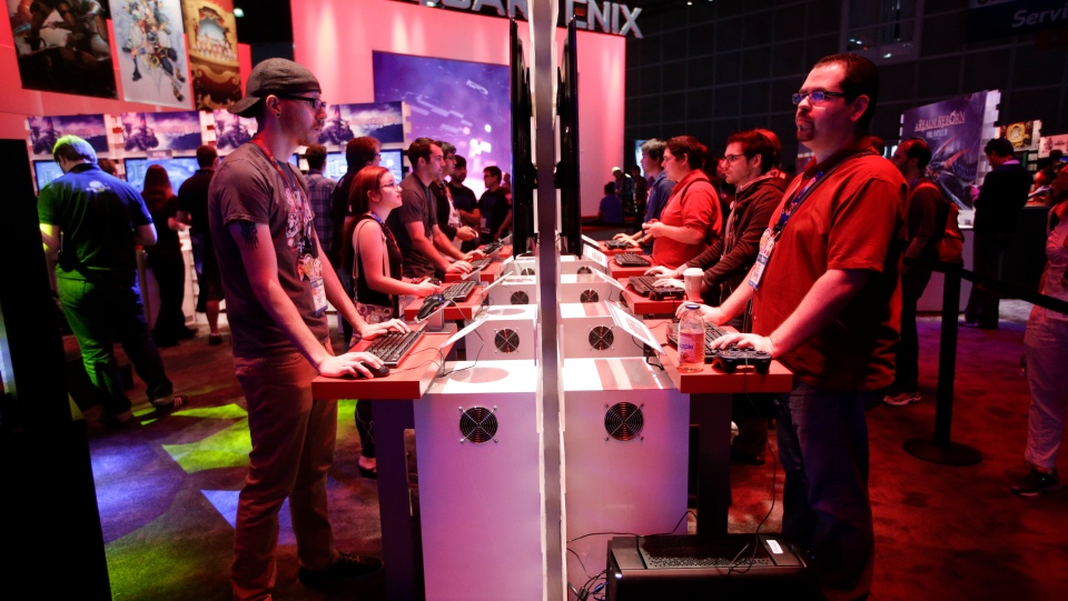 People play a video game at the Square Enix booth at the Electronic Entertainment Expo in Los Angeles on Thursday, June 12, 2014. (AP Photo/Jae C. Hong)