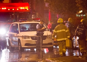 Police and fireman work at the rear of an auditorium where a gunman opened fire during the PQ victory rally on September 5, 2012, in Montreal. THE CANADIAN PRESS/Paul Chiasson