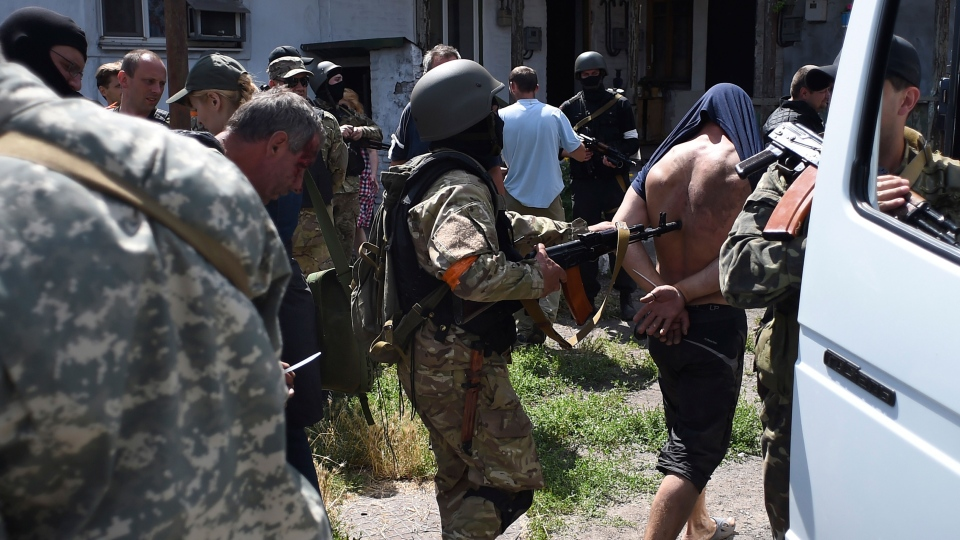 Ukrainian troops from battalion Azov escort to a bus, men detained at a site of battle with pro-Russian fighters in Mariupol, eastern Ukraine, Friday, June 13, 2014. (AP / Osman Karimov, pool)