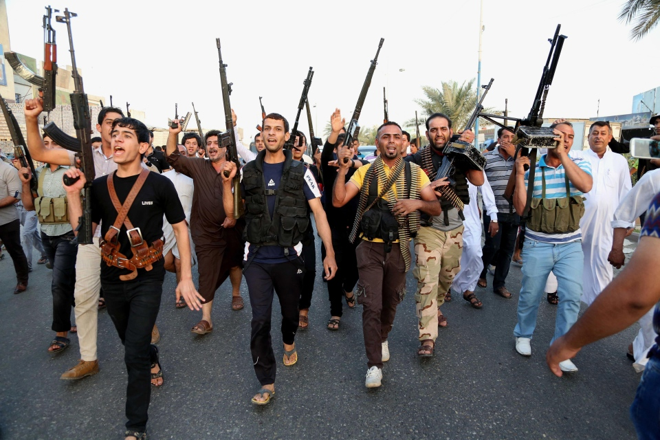 Iraqi Shiite tribal fighters deploy with their weapons while chanting slogans against the AL-Qaida inspired Islamic State of Iraq and the Levant (ISIL), to help the military, which defends the capital in Baghdad's Sadr City, Iraq, Friday, June 13, 2014. (AP Photo/ Karim Kadim)