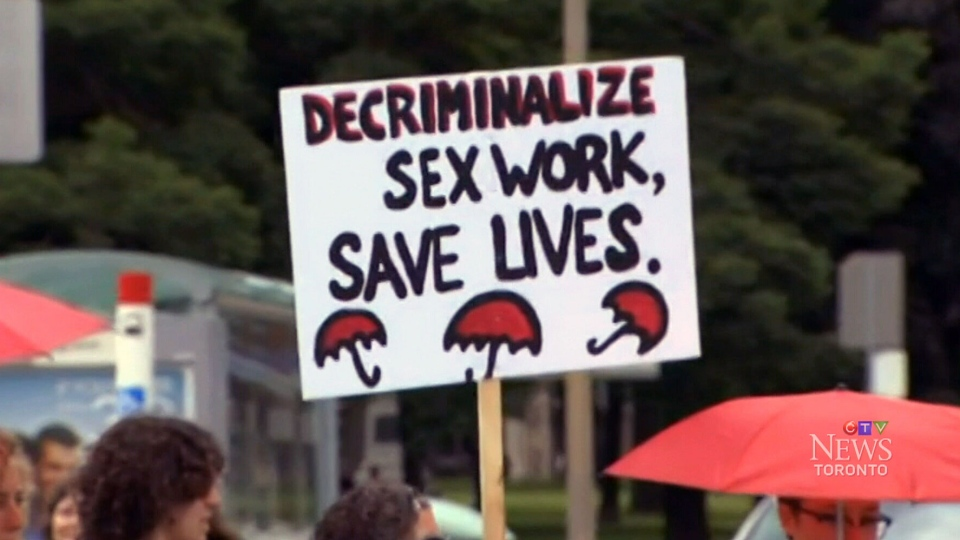 A protester holds a sign calling for the decriminalization of prostitution in Toronto, Saturday, June 14, 2014.
