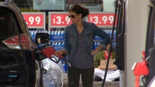 A woman is seen pumping gas