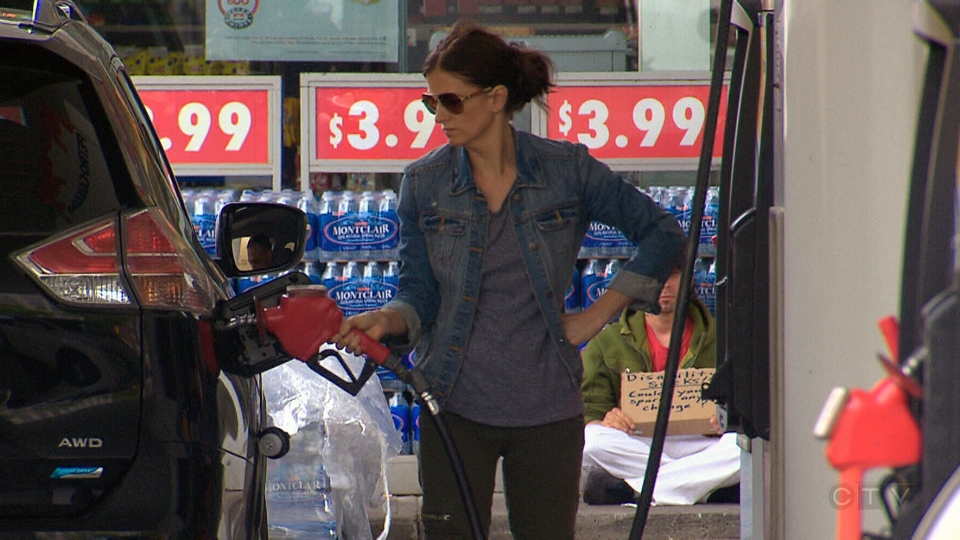 A woman is seen pumping gas at station in Montreal, Saturday, June 14, 2014.