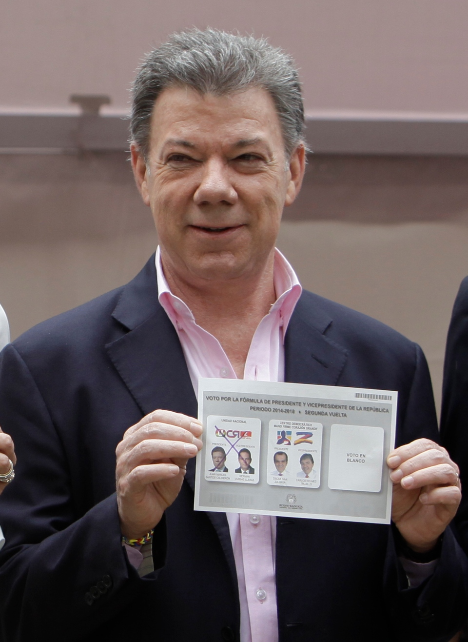 President Juan Manuel Santos shows his ballot before voting during presidential elections in Bogota, Colombia, Sunday, June 15, 2014. (AP / Javier Galeano)
