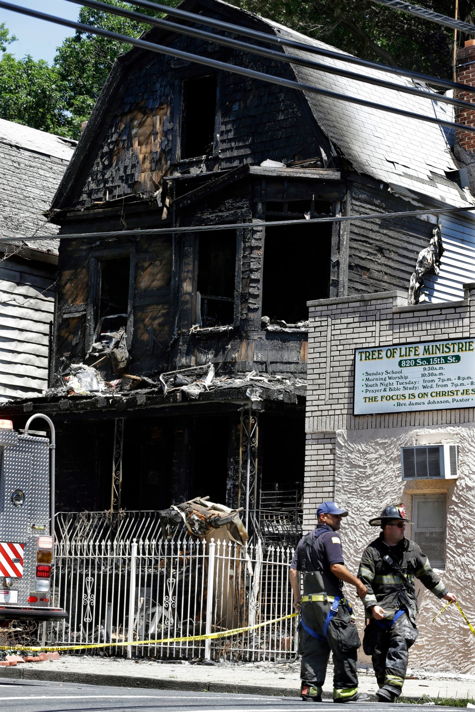 Firefighters and police work near the rubble of a burned-out home as they look for clues to a fire that authorities say killed six people in Newark, N.J., Sunday, June 16, 2014. (AP Photo/Mel Evans)