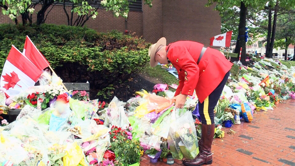 A Mountie helps remove the memorial outside RCMP HQ in Moncton, N.B.