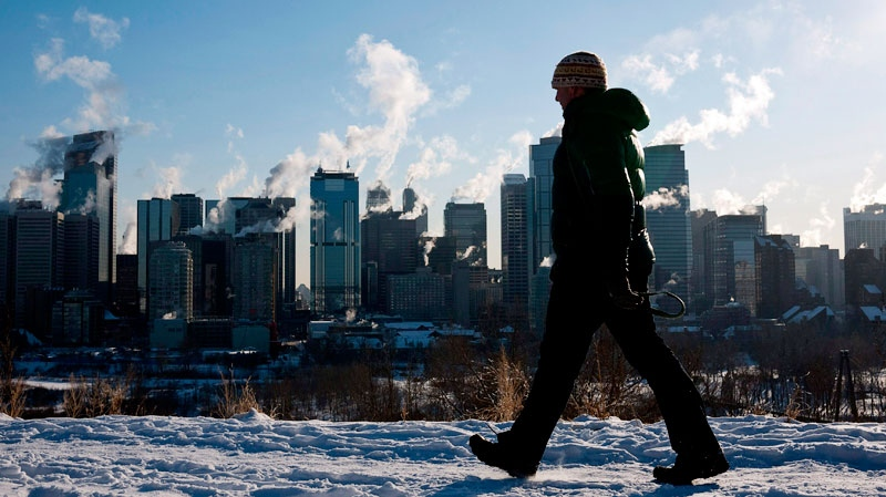 A man walks past a the Calgary, Alta., skyline during a deep freeze on Jan. 31, 2011. (Jeff McIntosh / THE CANADIAN PRESS)