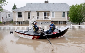 Two men use a fishing boat to rescue residents from a neighborhood after heavy rains caused flooding, closed roads, and forced evacuation in High River, Alta., Thursday, June 20, 2013. (Jeff McIntosh / THE CANADIAN PRESS)