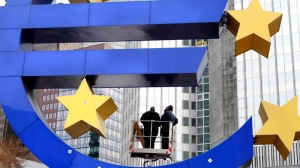 Workers change tube lights of the Euro sculpture in front of the European Central Bank in Frankfurt, Germany, Tuesday, Dec.6, 2011. (AP / Michael Probst)