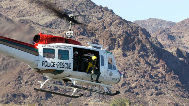 A Las Vegas Metropolitan Police rescue helicopter lift off carrying a scout team to the site of a tour helicopter crash to search for access to begin the recovery process in Las Vegas, Thursday, Dec. 8, 2011. (AP / Julie Jacobson)