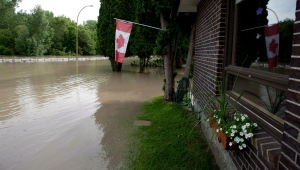 Floodwater surrounds homes on Harris Street in Medicine Hat, Alta., Monday, June 24, 2013. (Jonathan Hayward / THE CANADIAN PRESS)