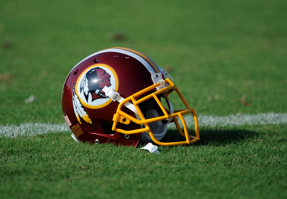 A Washington Redskins football helmet lies on the field during NFL football minicamp,  in Ashburn, Va., Wednesday, June 18, 2014. (AP / Nick Wass)