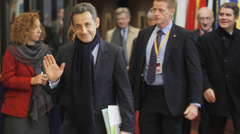 French President Nicolas Sarkozy, second left, leaves an EU summit in Brussels on Friday, Dec. 9, 2011. The president of the European Council said Friday that a new intergovernmental treaty meant to save the euro currency will include the 17 eurozone states plus as many as six other European Union countries, but not all 27 EU members. (AP Photo/Michel Euler)
