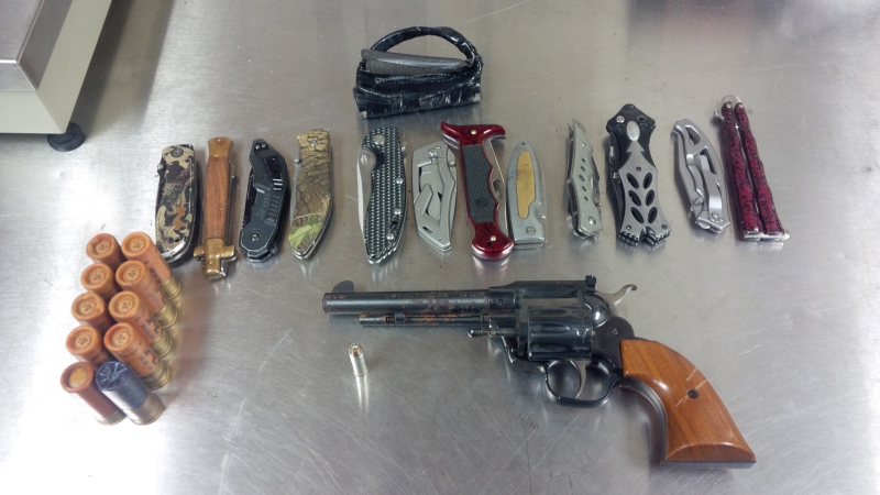 A handgun and prohibited knives seized from a home are seen in this photo released by the London Police Service.