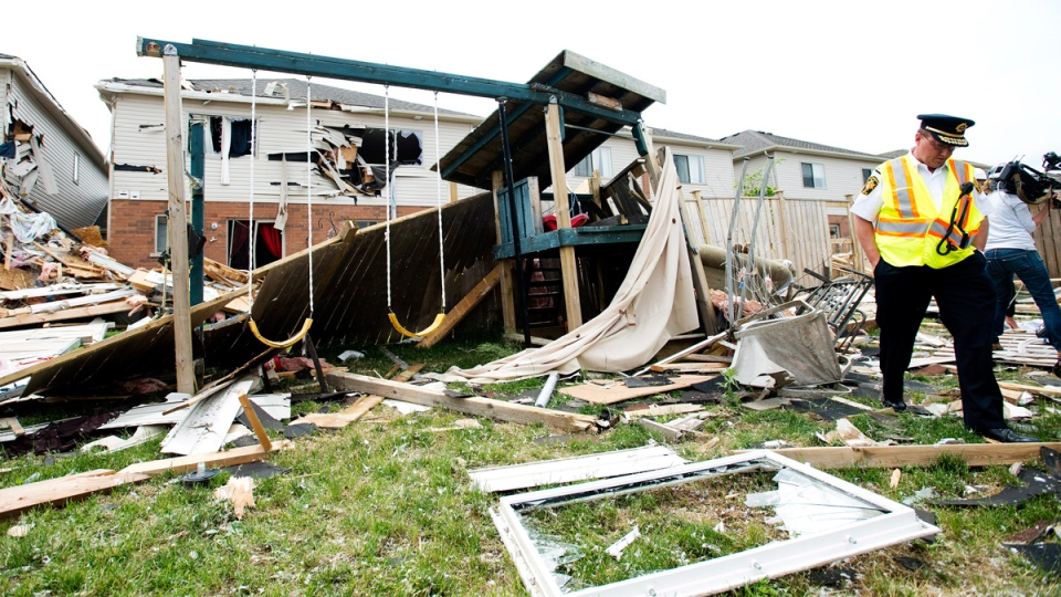 Investigators assess the damage to homes and property in Angus, Ont. on Wednesday, June 18, 2014. (Nathan Denette / THE CANADIAN PRESS)