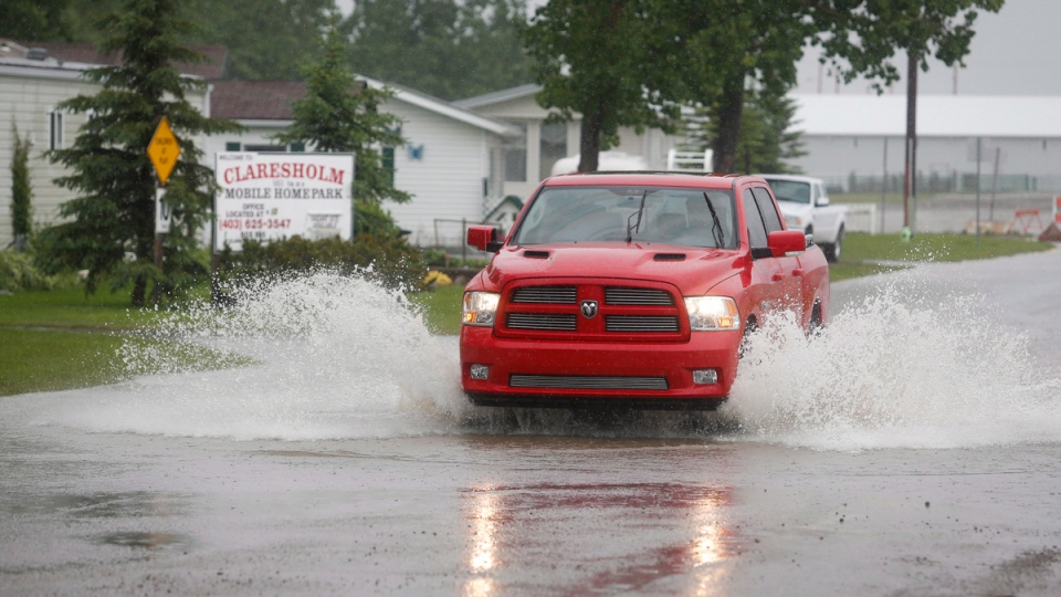 A truck sprays water as it's driven through flood waters in Claresholm, Alta., Wednesday, June 18, 2014. (Jeff McIntosh / THE CANADIAN PRESS)