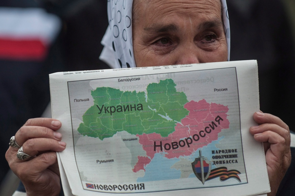 A woman holds a map of Ukraine divided into two parts, the eastern carrying the name Novorossia, or New Russia, during a rally in support of peace in Donetsk, eastern Ukraine on Wednesday, June 18, 2014. (AP / Evgeniy Maloletka)