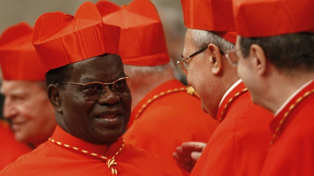 In this Saturday, Nov. 20, 2010 file photo, newly-appointed Cardinal Laurent Monsengwo Pasinya, of the Democratic Republic of Congo, left, is congratulated by other cardinals after being elevated by Pope Benedict XVI during a consistory inside St. Peter's Basilica, at the Vatican. (AP Photo/Pier Paolo Cito)