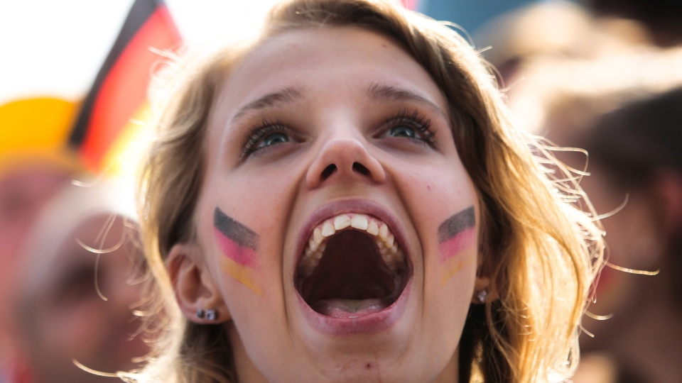 A German soccer fan celebrates their team's third goal during their first game at the World Cup 2014 at a public viewing zone called 'fan mile' in Berlin, Monday, June 16, 2014. (AP / Markus Schreiber)