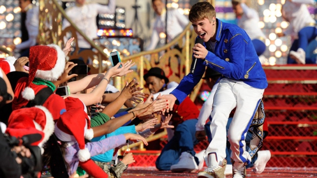 "In this photo provided by Disney, Justin Bieber performs while taping a segment for the ""Disney Parks Christmas Day Parade"" TV special at the Magic Kingdom park at Walt Disney World in Lake Buena Vista, Fla. on Saturday, Dec. 3, 2011. (AP Photo/Disney, Mark Ashman)"