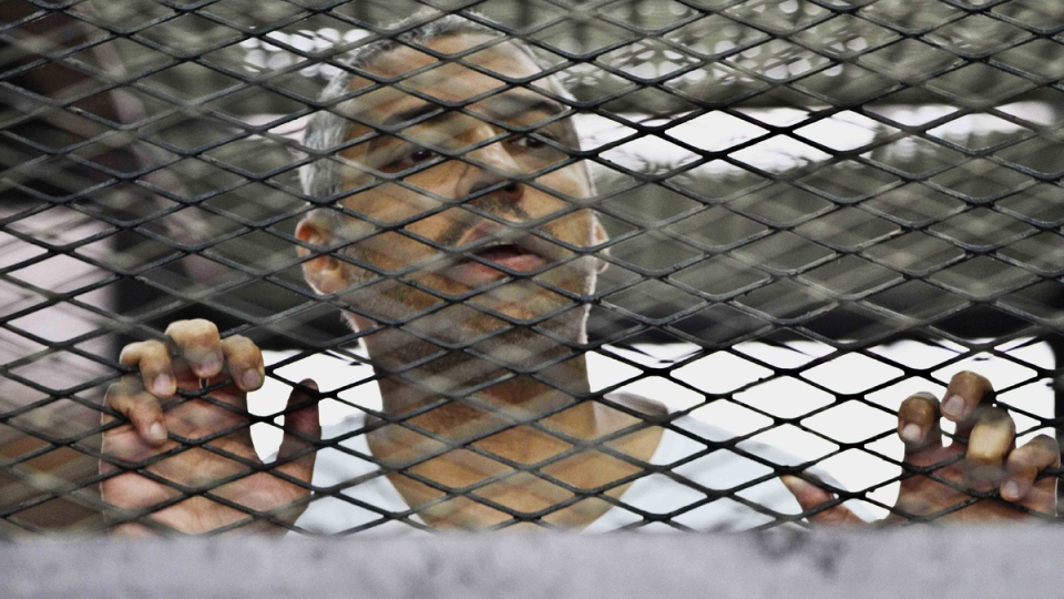 In this Thursday, May 5, 2014 photo, Canadian-Egyptian acting bureau chief of Al-Jazeera Mohammed Fahmy appears in a defendant's cage along with several other defendants during their trial on terror charges at a courtroom in Cairo, Egypt. (AP / Hamada Elrasam)
