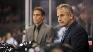 Coach Willie Desjardins, right, stands behind the bench in this file photo.