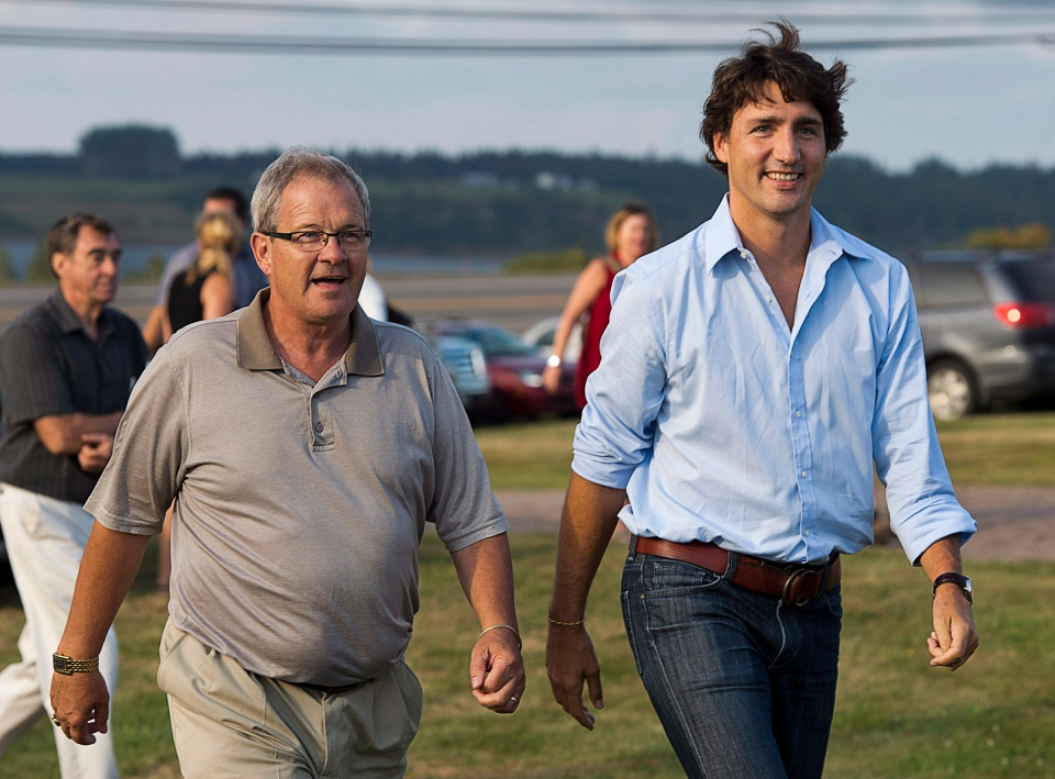 Justin Trudeau is welcomed by Cardigan MP Lawrence MacAulay to a barn party at his home in St. Peters Bay, P.E.I. on Wednesday, Aug. 28, 2013. (Andrew Vaughan / THE CANADIAN PRESS)