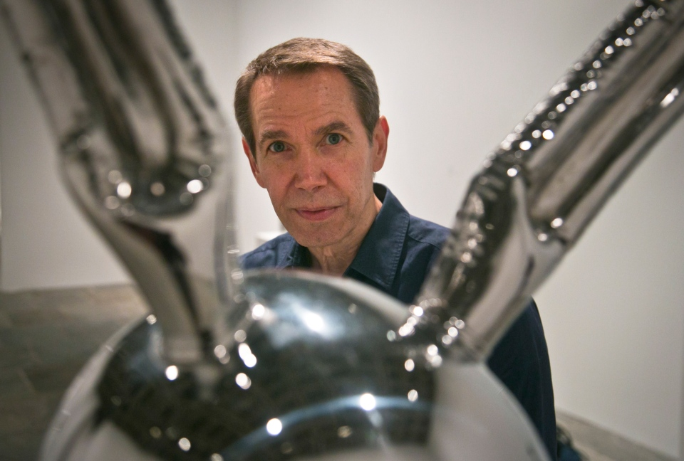 Jeff Koons poses next to Rabbit, one of his oversized toy-like sculptures among works spanning a 30-year career being installed at the Whitney Museum of American Art on Monday, June 23, 2014, in New York. (AP Photo/Bebeto Matthews)