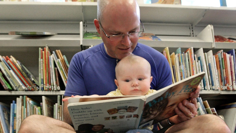 Mike Anderson reads to his six-month-old daughter Claire Anderson while participating in the Man in the Moon program at the South Hill branch of the Vancouver Public Library in Vancouver, B.C., on Thursday June 11, 2009. (THE CANADIAN PRESS/Darryl Dyck)