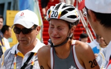 Lauren Groves, of Canada, grimaces after injuring her arm in a bike crash during the women's triathlon at the 2008 Beijing Olympics in Beijing, Monday, Aug. 18 , 2008. (AP Photo/Robert F. Bukaty)