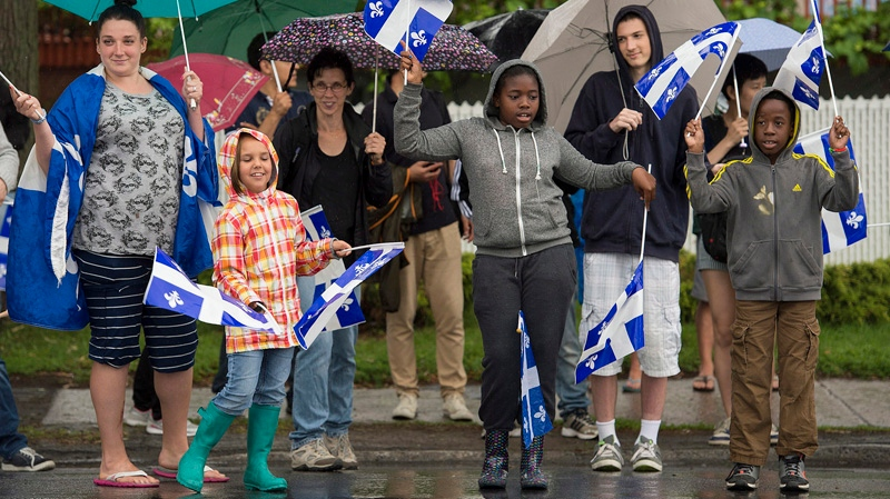 Members of the crowd wave flags as they enjoy the annual St-Jean-Baptiste Day parade in Montreal, Tuesday, June 24, 2014. THE CANADIAN PRESS/Graham Hughes