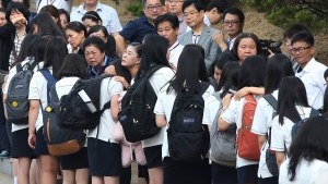 Students who survived the sinking of a ferry Sewol are comforted by parents of their friends who lost their lives in the disaster as they make their way back for their first class since the disaster in Ansan, South Korea, Wednesday, June 25, 2014. (Yonhap)