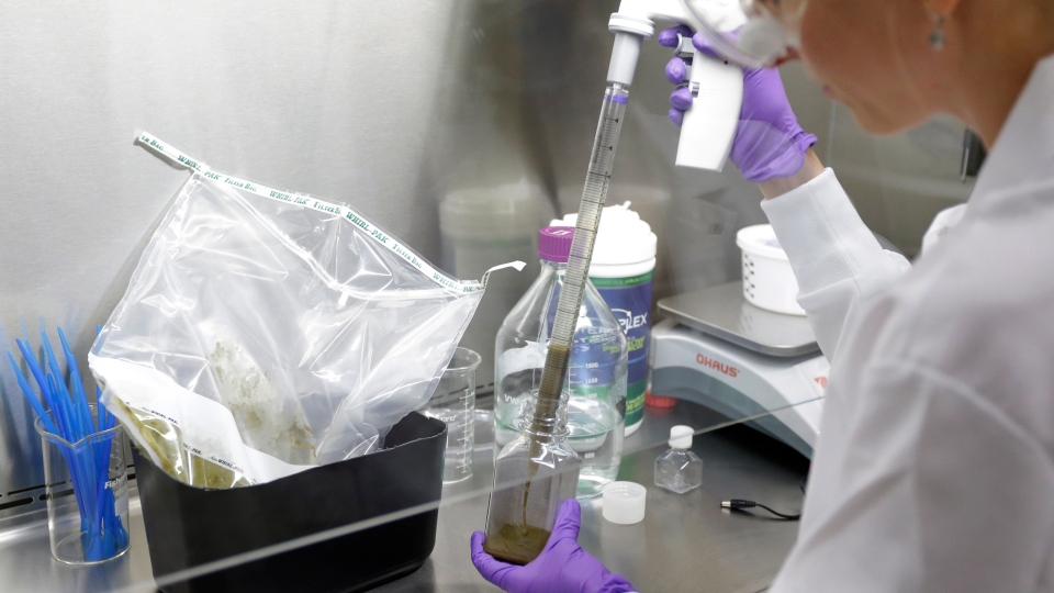 In this Thursday, June 19, 2014 photo, technical assistant Eliska Didyk transfers human fecal matter solution into a bottle in an OpenBiome laboratory, in Medford, Mass. (AP Photo/Steven Senne)