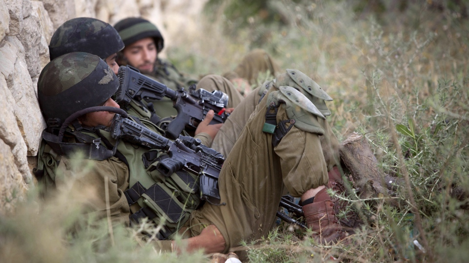 Israeli soldiers take a break as they search for three missing Israeli teens, feared abducted in the West Bank last week, in the village of Beit Kahil near the West Bank city of Hebron, Saturday, June 21, 2014. (AP / Majdi Mohammed)