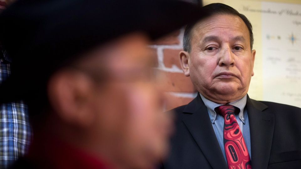 Grand Chief Stewart Phillip, right, of the Union of B.C. Indian Chiefs, listens as Chief Roger William, of the Xeni Gwet'in First Nation, speaks during a news conference in Vancouver, after the Supreme Court of Canada ruled in favour of the Tsilhqot'in First Nation, granting it land title to 438,000-hectares of land on Thursday June 26, 2014. (Darryl Dyck / THE CANADIAN PRESS)